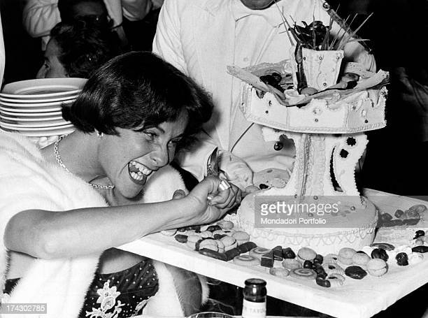 Italian actress Alida Valli having fun touching a cake on the occasion of Grolla d'Oro Prize 1955 SaintVincent July 1955