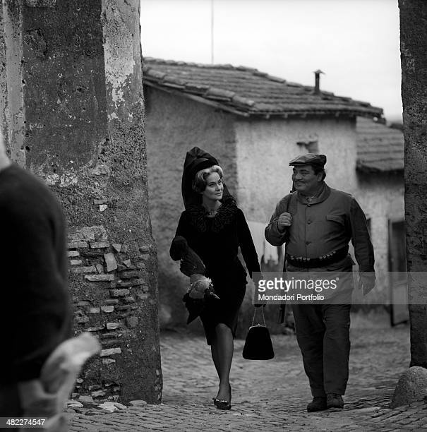 Italian actress Alida Valli holding a dead bird walking beside Italian actor and partisan Folco Lulli with a rifle in the film Umorismo in nero Italy...