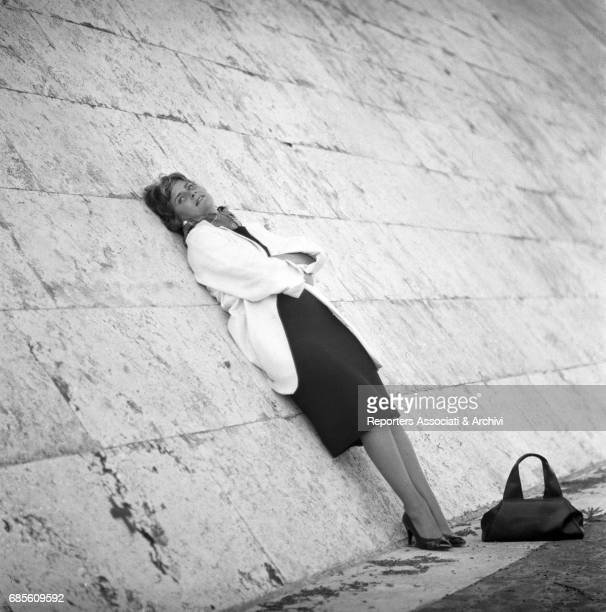 Italian actress Alida Valli lying on a wall 1959