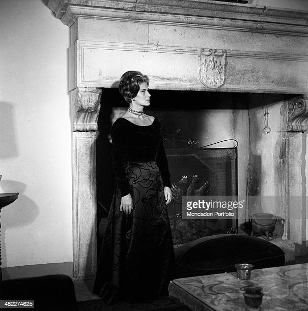 Italian actress Alida Valli posing in front of a fireplace decorated with a six lilies escutcheon Italy 1960s