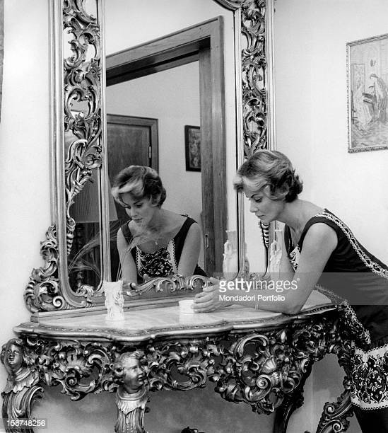 Italian actress Alida Valli posing while she's leaning on the marble top of a decorated console made of inlaid golden wood Her image is reflected in...