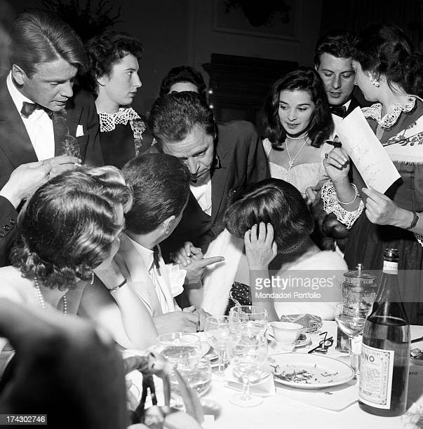 Italian actress Alida Valli sitting at the table surrounded by some people on the occasion of Grolla d'Oro Prize 1955 SaintVincent July 1955
