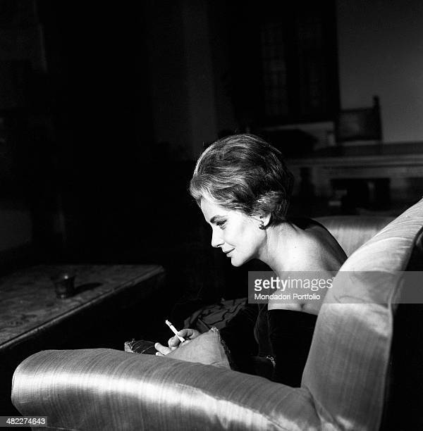 Italian actress Alida Valli sitting on a sofa and smoking a cigarette Italy 1960s
