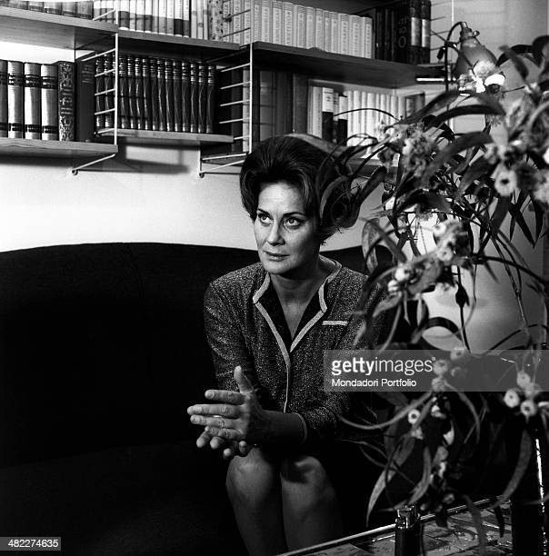 Italian actress Alida Valli sitting on a sofa in the livingroom in front of a bookcase Italy 1960s