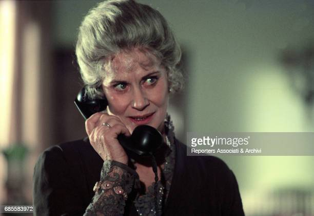 Italian actress Alida Valli smiling and holding a bakelite phone handset in a scene from the film 'The Perfect Crime' directed by Giuseppe Rosati...