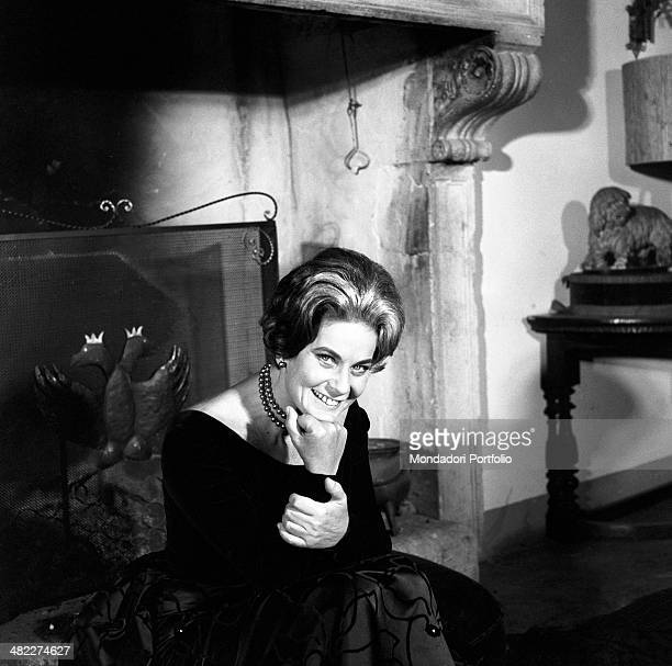 Italian actress Alida Valli smiling in front of a fireplace in front of a fire screen decorated by a twoheaded eagle Italy 1960s