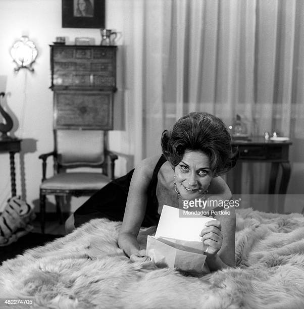 Italian actress Alida Valli smiling lying on a bed with a letter in the hands Italy 1960s