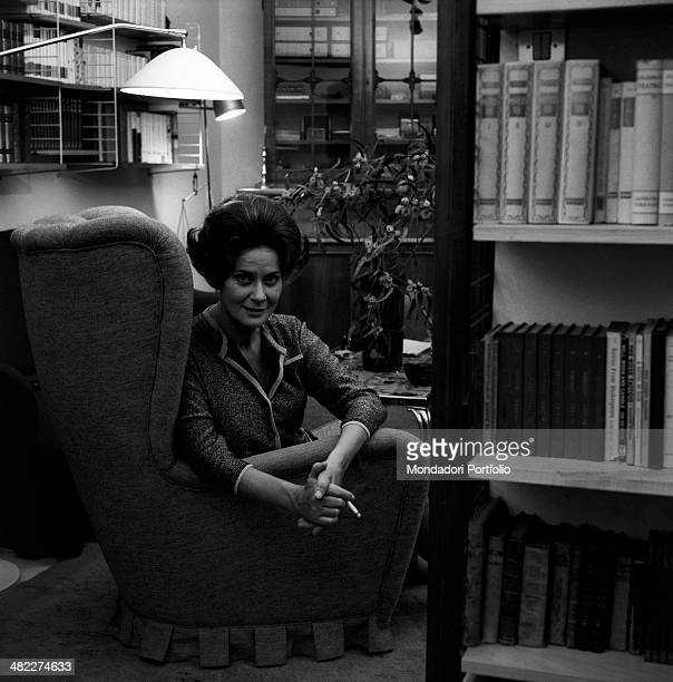 Italian actress Alida Valli smoking a cigarette seated on an armchair Italy 1960s