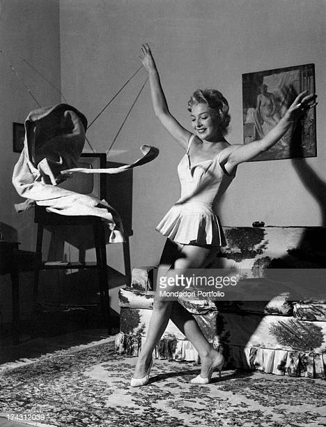 Italian actress and dubber Isa Barzizza in petticoat throwing a jacket 1950s