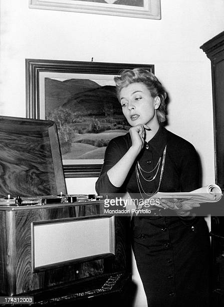 Italian actress and dubber Isa Barzizza listening a record holding a notebook 1950s