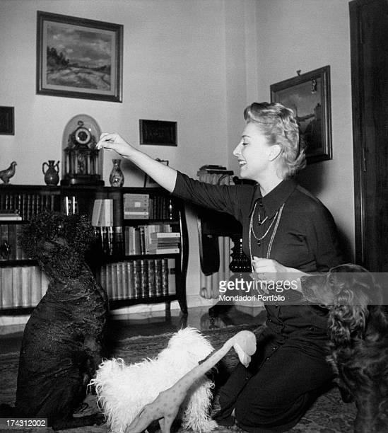 Italian actress and dubber Isa Barzizza playing with some dogs 1950s