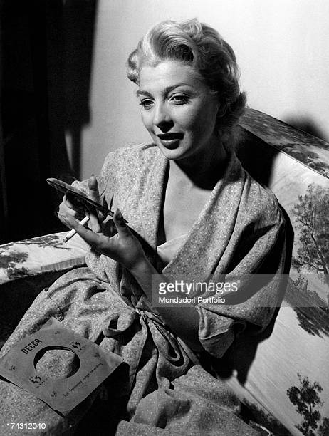 Italian actress and dubber Isa Barzizza smoking holding a record 1950s