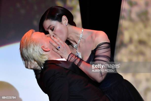 Italian actress and master of ceremonies Monica Bellucci and French comedian Alex Lutz kiss as they perform on stage on May 17 2017 during of the...