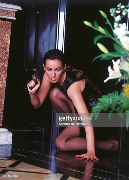 Italian actress and Miss Italy in 1977 Anna Kanakis holding a weapon in her hand. 1999