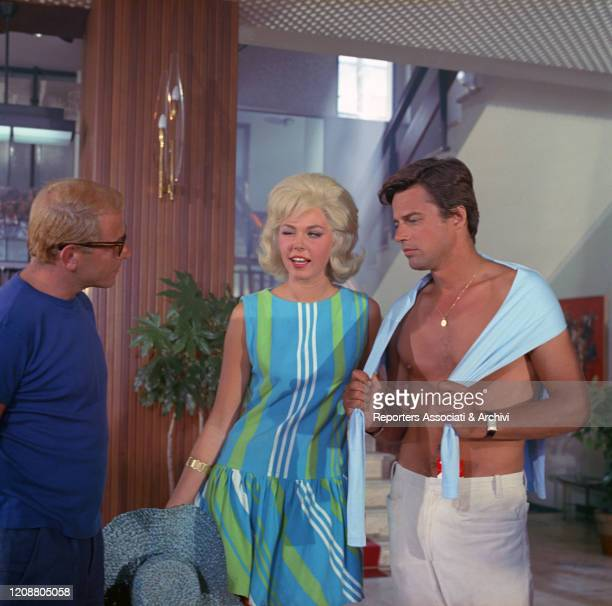 Italian actress and model Daniela Bianchi arm in arm with French actor Jean Sorel and winking at Italian actor Enrico Maria Salerno in the film...
