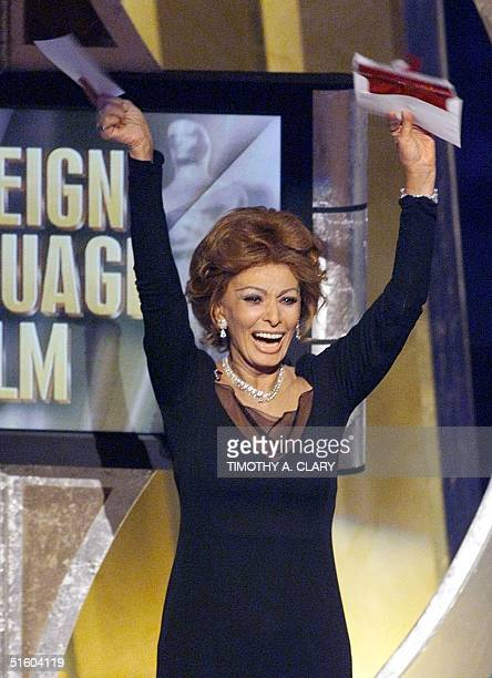 Italian actress and presenter Sophia Loren celebrates after reading the name of Italian director Roberto Benigni in winning the Oscar for Best...