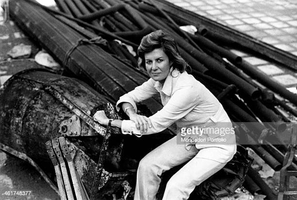 Italian actress and scriptwriter Marina Cicogna wearing white pants and jacket with belt of the same colour sits among pipes and junkers...