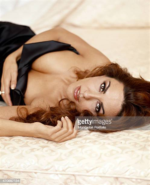 'Italian actress and sex symbol Sabrina Ferilli in a provocative pose lying in a bed directing an intense gaze to the camera '