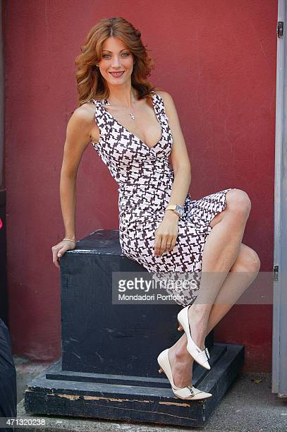 Italian actress and showgirl Milena Miconi as the maior of the city in Umbria posing seated with crossed legs on a black cube in a photo shooting on...