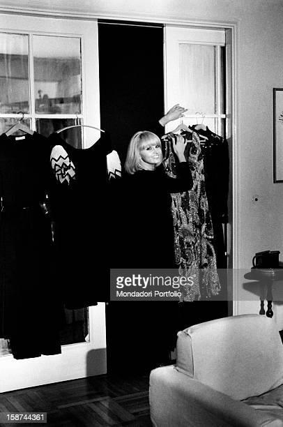 Italian actress and singer Carmen Villani arranging some dresses Milan 1970s