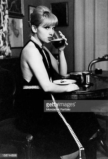 Italian actress and singer Carmen Villani sitting at a table and drinking Milan 1970s