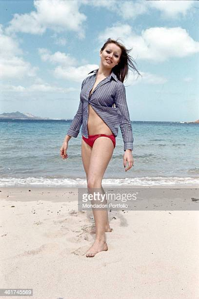Italian actress and singer Gloria Guida posing at the beach wearing a striped shirt and a red swimsuit. Italy, 1972