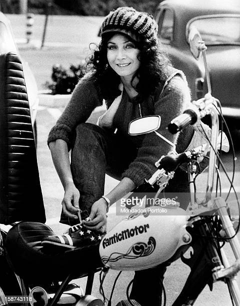 Italian actress and singer Maria Grazia Buccella lacing up her shoes putting her leg on the saddle of a motorcycle Rome 1970s