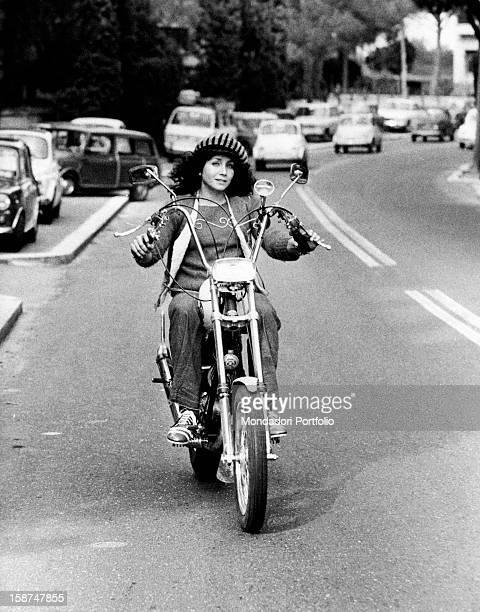 Italian actress and singer Maria Grazia Buccella riding a motorcycle Rome 1970s