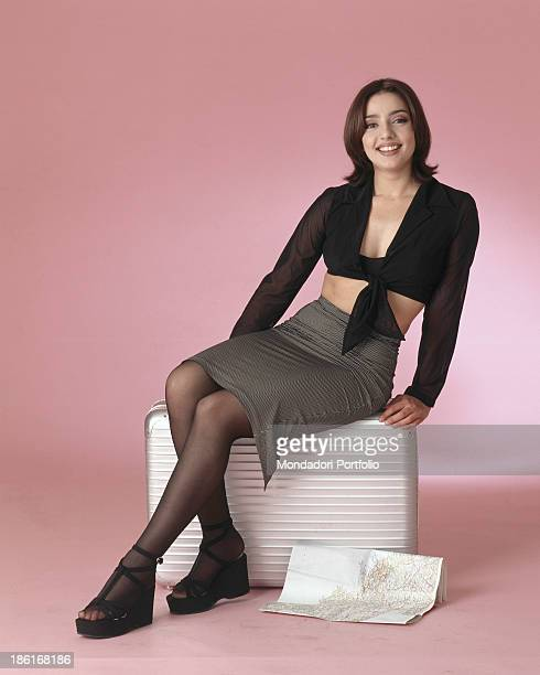 Italian actress and TV presenter Ambra Angiolini sitting on a stool Italy 1996