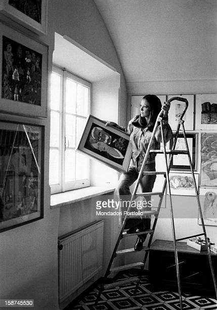 Italian actress and TV presenter Laura Efrikian going up a ladder and hanging a painting. Rome, 1970s