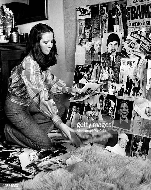 Italian actress and TV presenter Laura Efrikian on her knees arranging some photos and press-cuttings. Rome, 1970s