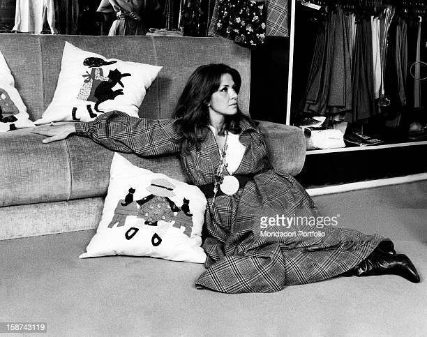 Italian actress and TV presenter Laura Efrikian sitting on the floor and leaning on a sofa. Rome, 1970s