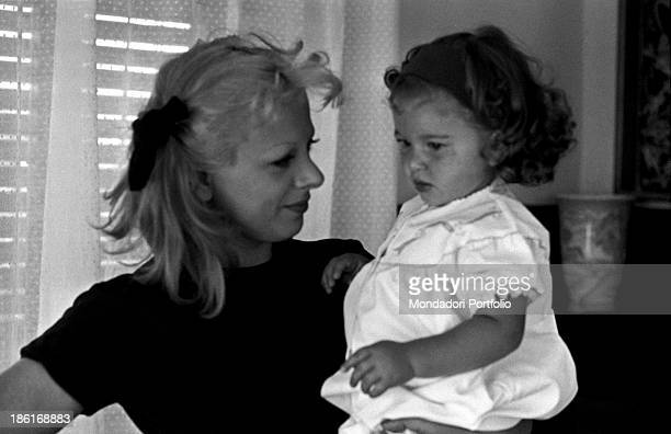 Italian actress and TV presenter Sandra Milo holding her daughter Azzurra De Lollis at home Fregene July 1964