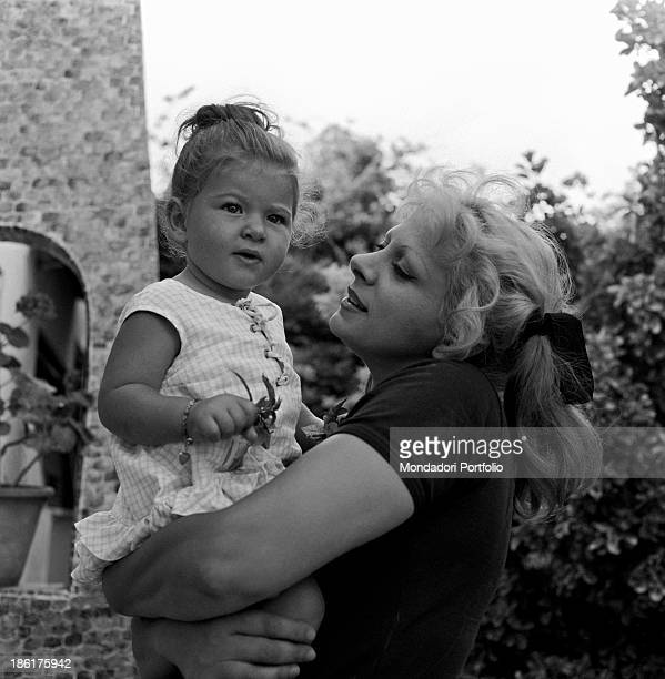 Italian actress and TV presenter Sandra Milo holding her daughter Azzurra De Lollis in her garden at home Fregene July 1964