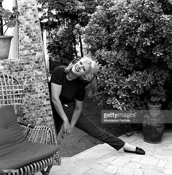 Italian actress and TV presenter Sandra Milo smiling parting her legs in her garden at home Fregene July 1964