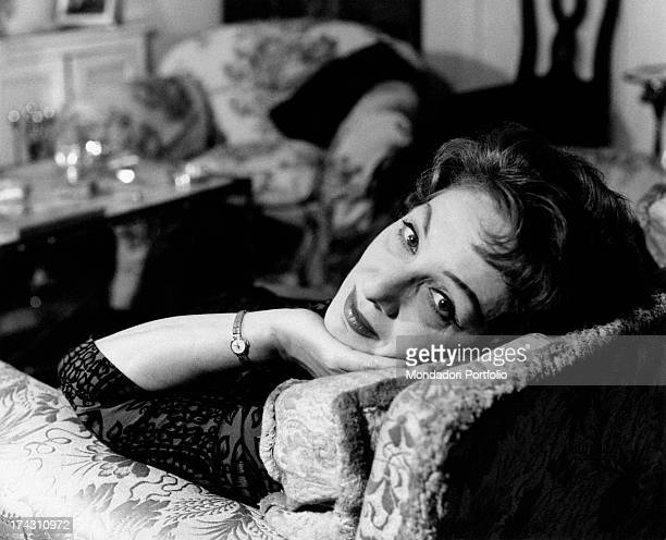 Italian actress Andreina Pagnani leaning on the fireplace in her house Rome 1964