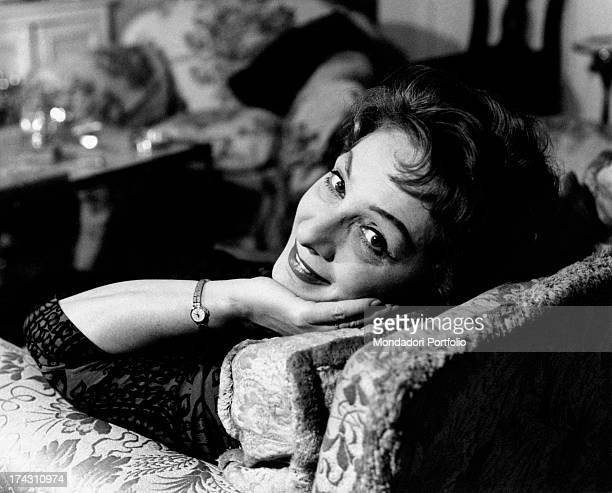 Italian actress Andreina Pagnani reading a book in the living room of her house Rome 1964
