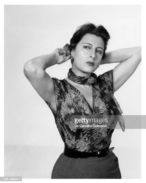Italian Actress Anna Magnani as 'Serafina Delle Rose' in a floral outfit and attaching a flower to her head in the role that gave her an Oscar...