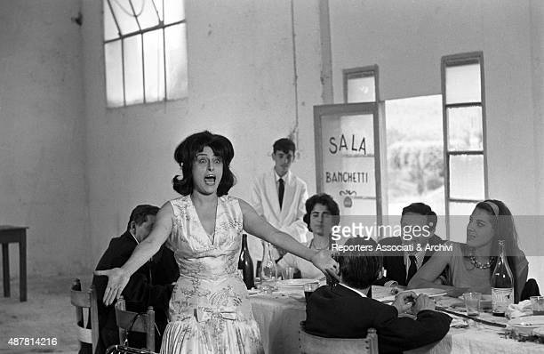 Italian actress Anna Magnani singing at a wedding lunch in the film Mamma Roma Rome 1962