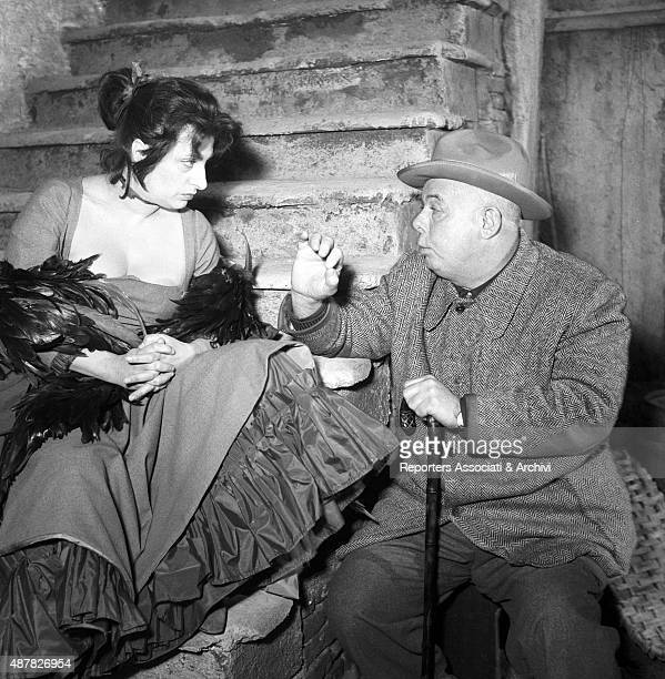 Italian actress Anna Magnani taking a break with French director Jean Renoir on the set of The Golden Coach Italy 1952