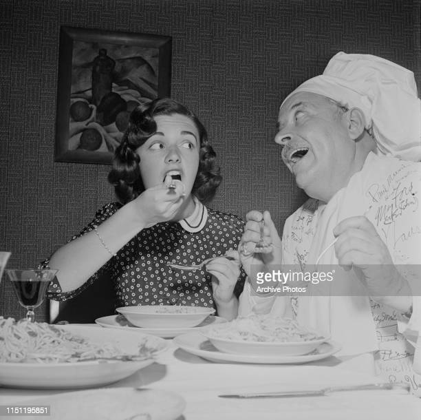 Italian actress Anna Maria Alberghetti eating spaghetti made by a chef with an autographed apron 1953