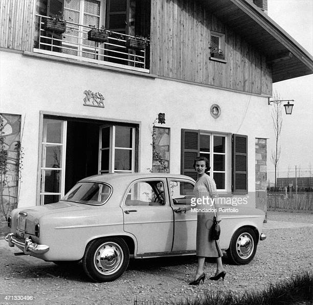 Italian actress Anna Maria Ferrero opening the door of an Alfa Romeo Giulietta Milan April 1955