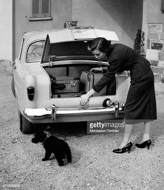 Italian actress Anna Maria Ferrero putting her luggage into an Alfa Romeo Giulietta Milan April 1955