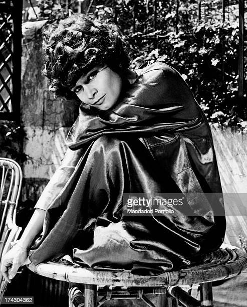 Italian actress Anna Maria Guarnieri in the garden wearing a silk dressing gown sitting on a wooden table Rome May 1968