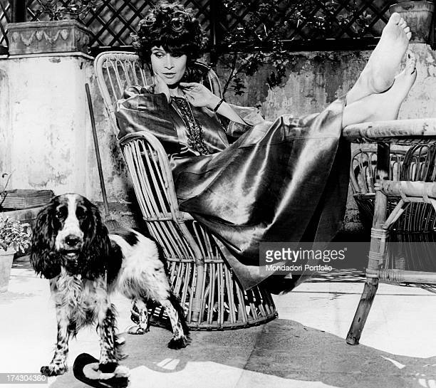 Italian actress Anna Maria Guarnieri sitting in the garden in a wooden chair leaning her bare feet on the table in company of her dog Rome May 1968