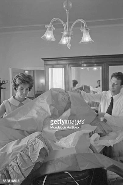 Italian actress Antonella Lualdi and her husband and Italian actor Franco Interlenghi opening the boxes with the evening dress during the 19th Venice...