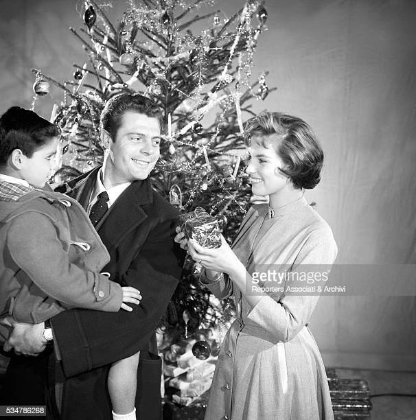Italian actress Antonella Lualdi giving a gift to the child held by Italian actor Marcello Mastroianni in the film Fathers and Sons 1956