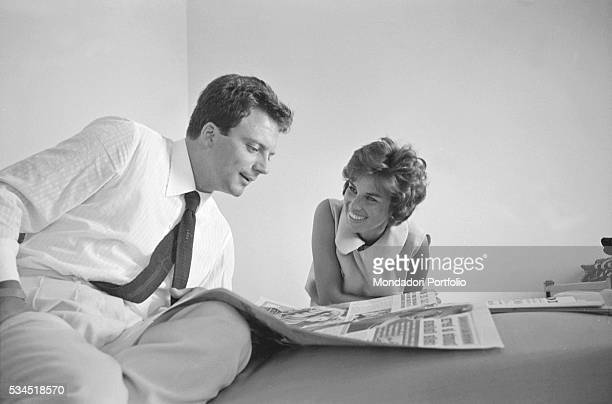 Italian actress Antonella Lualdi looking at her husband and Italian actor Franco Interlenghi reading a newspaper during the 19th Venice International...