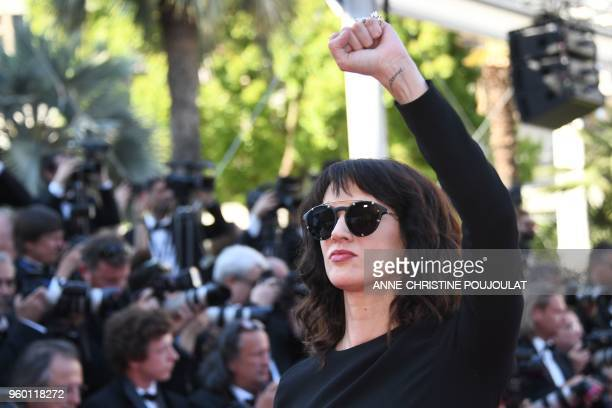 Italian actress Asia Argento raises her fist as she arrives on May 19 2018 for the closing ceremony and the screening of the film The Man Who Killed...
