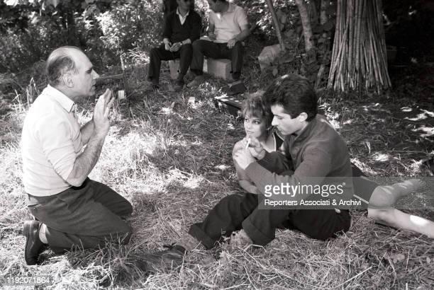 Italian actress Claudia Cardinale and American actor Georges Chakiris preparing a scene on the set of La Ragazza di Bube with Italian director Luigi...